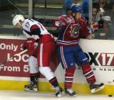 Max Nicastro of the Grand Rapids Griffins and a Hamilton Bulldog recoil after a collision along the boards.