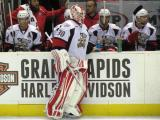 Tom McCollum stands at the bench during a stoppage in place in a Grand Rapids Griffins game, along with Brennan Evans, Max Nicastro and Brian Lashoff.