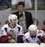 Grand Rapids assistant coach Jim Paek stands behind Brian Lashoff and Chad Billins on the Griffins' bench.