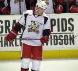 Triston Grant examines his stick during a stop in play in a Grand Rapids Griffins game.
