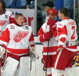 Chris Osgood yawns while talking to Chris Chelios and Jiri Fischer prior to the starts of an alumni game, with Bill Gadsby on the bench behind them.