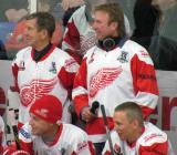 Ted Lindsay and Eddie Mio stand behind Darren McCarty and Igor Larionov at the bench during an alumni game.