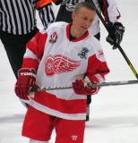 Igor Larionov takes a look at his stick during a stop in play in an alumni game.