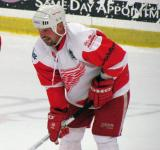 Joe Kocur laughs while getting set for a faceoff in an alumni game.