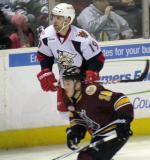 Riley Sheahan of the Griffins skates up the boards alongside Jordan Schroeder of the Wolves in a game between Grand Rapids and Chicago.