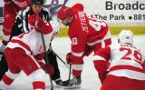 Henrik Zetterberg of the Red Team takes a faceoff against Valtteri Filppula and Mike Knuble of the White Team during the Red and White Game.