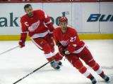 Kyle Quincey turns in the neutral zone during pre-game warmps, with Henrik Zetterberg behind him.