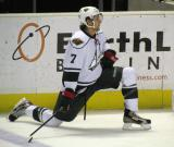 Kris Fredheim of the Houston Aeros stretches along the boards during pre-game warmups before a game against the Grand Rapids Griffins.