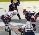 Riley Sheahan lines up across from Joey Tenute of the Hamilton Bulldogs for a faceoff during the Grand Rapids Griffins' Purple Game, with Francis Pare and Patrick Holland on their respective wings.