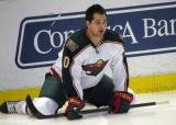 Devin Setoguchi of the Minnesota Wild stretches along the boards during pre-game warmups before a game against the Detroit Red Wings.