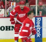 Drew Miller stands along the boards as Ian White cuts in front of him.