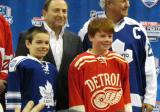 Andrew Park and Kienan Draper display the jerseys to be worn by the Toronto Maple Leafs and Detroit Red Wings in the 2014 Winter Classic at the announcement press conference, with Gary Bettman and Darryl Sittler behind them.