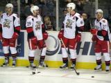 Landon Ferraro and Brennan Evans laugh at the boards during pre-game warmups before a Grand Rapids Griffins game, with Brent Raedeke standing to one side and Tomas Tatar bouncing a puck on his stick on the other.