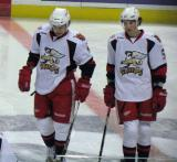 Francis Pare and Adam Almquist stand at center ice during pre-game warmups before a Grand Rapids Griffins game.