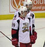 Jan Mursak and Brennan Evans look to the bench during a stop in play in a Grand Rapids Griffins game.