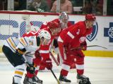 Daniel Alfredsson and Brendan Smith line up for a faceoff opposite Buffalo's Mikhail Grigorenko, in front of Detroit goalie Jimmy Howard.