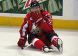 Triston Grant sits on the ice, stretching, during pre-game warmups before a Grand Rapids Griffins game.