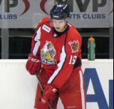 Xavier Ouellet plays with a puck at the boards during pre-game warmups before a Grand Rapids Griffins game.