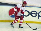 Adam Almquist carries a puck along the boards during pre-game warmups before the Grand Rapids Griffins play at Comerica Park.