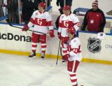 Mitch Callahan, Triston Grant and Brennan Evans stand at the blue line during pre-game warmups before the Grand Rapids Griffins play at Comerica Park.