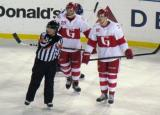 Landon Ferraro, Cory Emmerton, and referee Geno Binda look towards the bench during a stop in play in a Grand Rapids Griffins game at Comerica Park.