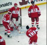 Chris Osgood stands in the crease with Kris Draper and Kirk Maltby to either side and Vyacheslav Kozlov taking a shot during pre-game warmups before the second game of the Alumni Showdown.
