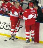 Mickey Redmond and Viacheslav Fetisov stand at the bench before the overtime period of the second Alumni Showdown game.