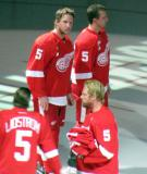 Justin Abdelkader, Luke Glendening and Johan Franzen stand on the ice during Nicklas Lidstrom's jersey retirement ceremony, wearing Lidstrom's #5 jersey.