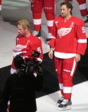 Johan Franzen and Kyle Quincey stand on the ice during Nicklas Lidstrom's jersey retirement ceremony, wearing Lidstrom's #5 jersey.