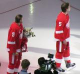Niklas Kronwall and Justin Abdelkader stand on the ice during Nicklas Lidstrom's jersey retirement ceremony, wearing Lidstrom's #5 jersey.