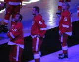 Todd Bertuzzi, Luke Glendening and Teemu Pulkkinen watch a video package from ice level during Nicklas Lidstrom's jersey retirement ceremony, wearing Lidstrom's #5 jersey.