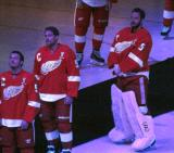 Gustav Nyquist, Joakim Andersson and Jonas Gustavsson watch a video package from ice level during Nicklas Lidstrom's jersey retirement ceremony, wearing Lidstrom's #5 jersey.