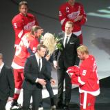 Niklas Kronwall presents Annika Lidstrom with flowers while Johan Franzen gives jerseys to the Lidstrom sons as the Lidstrom family enters Nicklas Lidstrom's jersey retirement ceremony.