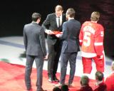 Pavel Datsyuk, Henrik Zetterberg and Niklas Kronwall present Nicklas Lidstrom with a team gift during Lidstrom's jersey retirement ceremony.