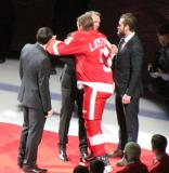 Niklas Kronwall and Nicklas Lidstrom hug as Kronwall, Pavel Datsyuk and Henrik Zetterberg present Lidstrom with a team gift during Lidstrom's jersey retirement ceremony.
