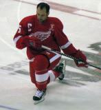 David Legwand kneels at center ice during pre-game warmups, wearing Nicklas Lidstrom's jersey in honor of its retirement.