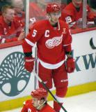 Tomas Jurco stands along the boards during pre-game warmups, wearing Nicklas Lidstrom's jersey in honor of its retirement.