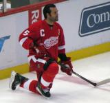 Todd Bertuzzi kneels along the boards during pre-game warmups, wearing Nicklas Lidstrom's jersey in honor of its retirement.