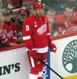 Johan Franzen stands at the boards during pre-game warmups, wearing Nicklas Lidstrom's jersey in honor of its retirement.