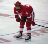Jonathan Ericsson crouches near center ice during pre-game warmups, wearing Nicklas Lidstrom's jersey in honor of its retirement.
