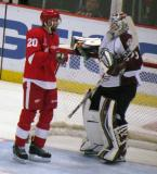 Drew Miller talks to Colorado goalie Jean-Sebastien Giguere during a stop in play.