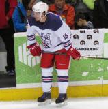 Xavier Ouellet crouches near the bench during pre-game warmups before the Grand Rapids Griffins' Purple Game.