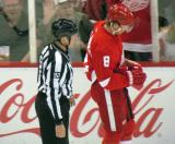 Justin Abdelkader is escorted to the penalty box by linesman Mark Shewchyk.