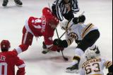 Luke Glendening takes a faceoff against Patrice Bergeron of the Boston Bruins.