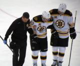 Brad Marchand of the Boston Bruins is helped off the ice by teammate Jarome Iginla and a trainer.