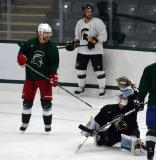 Jeff Lerg raises his glove to attempt a save while Jakub Kindl and Patrick Eaves look on during a session at the 2014 MSU Pro Camp.