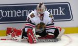 Antti Raanta of the Chicago Blackhawks stretches along the boards during pre-game warmups before a preseason game against the Detroit Red Wings.