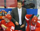 Assistant Coach Jim Hiller stands behind Tomas Jurco and Riley Sheahan at the Detroit bench during a preseason game.