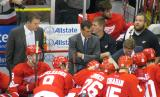 Detroit head coach Mike Babcock diagrams a play during a time out in a preaseason game, with assistants Jim Hiller and Tony Granato looking on.