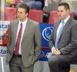 Assistant coaches Jim Hiller and Andrew Brewer stand at the Red Wings' bench during pre-game warmups.